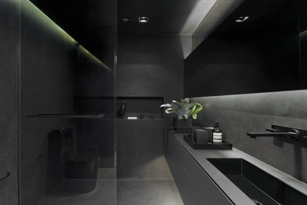 The bathroom is all gray with black fixtures and matching accessories. This gives it a super cool look