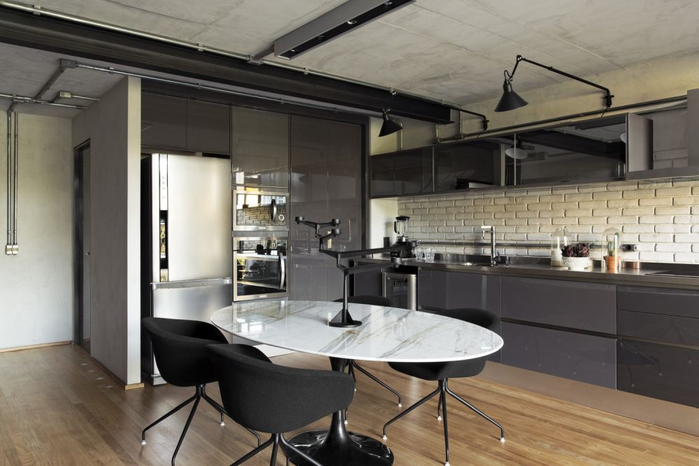 The dark gray on the walls and some of the furniture is complemented by the warm wooden floors