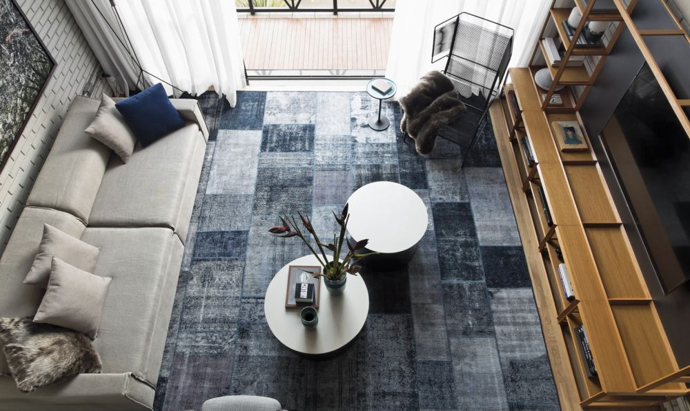 The blue hues on the living room area rug are in tone with the overall masculine vibe