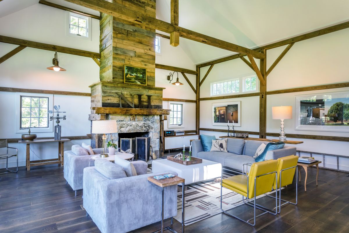 The stone fireplace with a rustic wood surround creates a cohesive decor in combination with the exposed beams