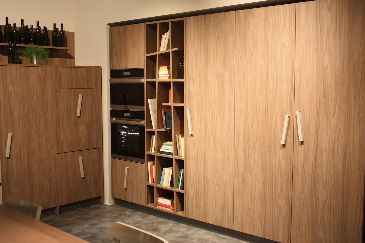 The skewed bar pulls in this Creo cabinetry mimic the off-kilter angles of the bookcase.