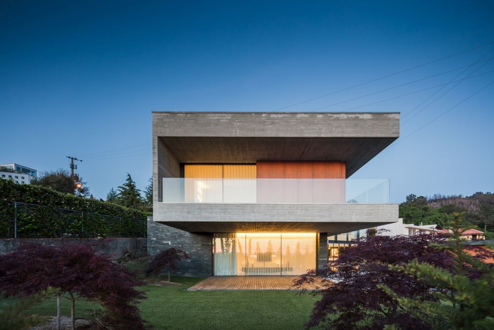 Floor-to-ceiling windows open up the house to its surroundings, allowing natural light to enter the rooms