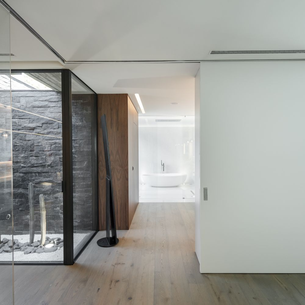Beautiful wood flooring and white walls ensure a nice fluidity throughout the house, connecting all the different functions