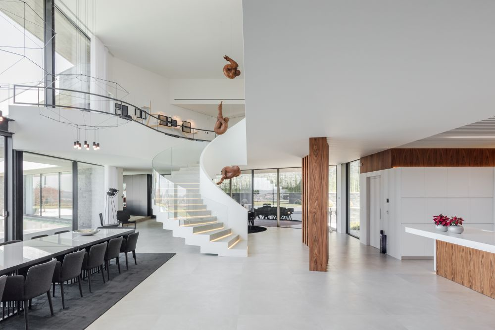 A graceful spiral staircase connects the ground floor to the upper level. It looks like a beautiful, giant sculpture
