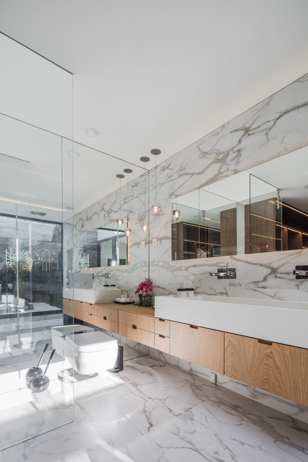The master bathroom features an eclectic design with marble walls and flooring and large mirrors