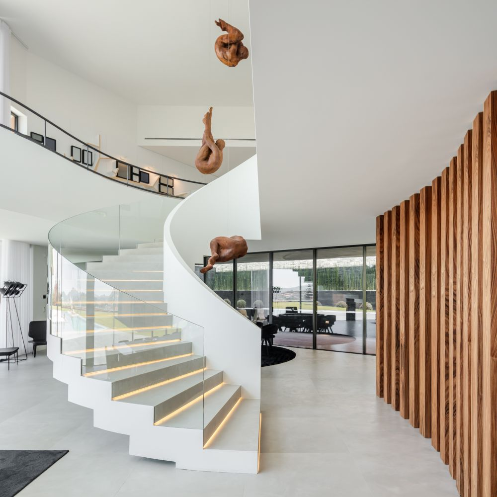 The spiral staircase has LED light strips on each step and a transparent glass outer railing