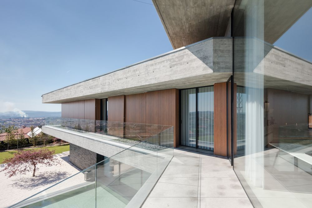 The private volumes are frame by long open balconies with glass railings