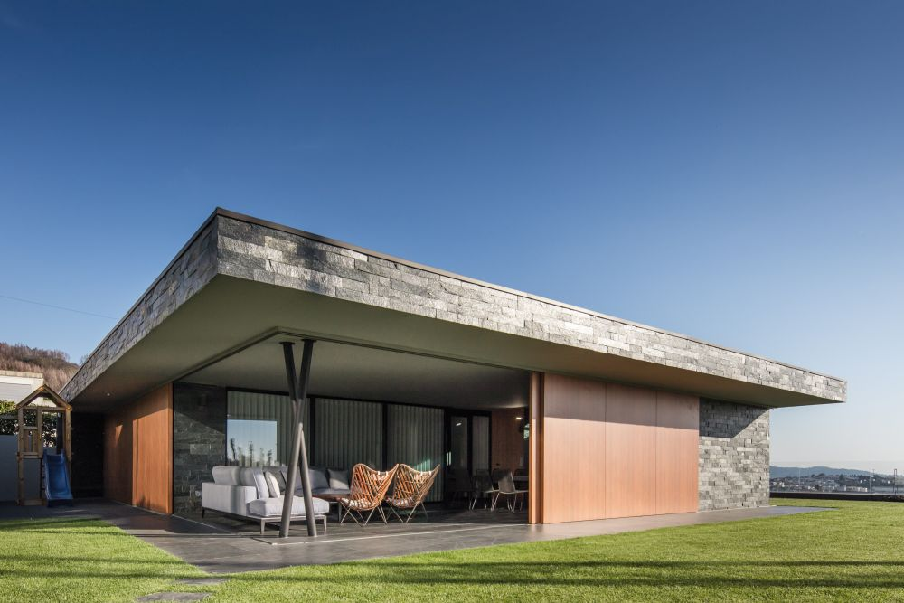 The ground floor living spaces feature large sliding doors and walls which expose them to the landscape and the views