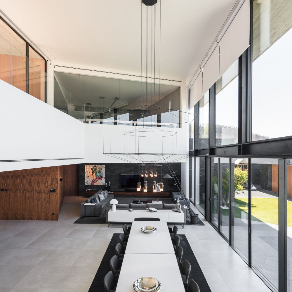 At the core of the house stands a double-height volume with a gorgeous, low-hanging chandelier