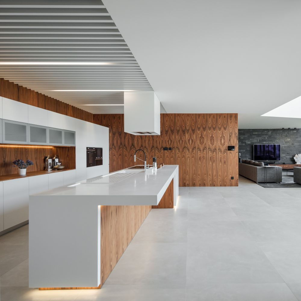 The kitchen is part of the open plan social area but is positioned outside of the double-height volume