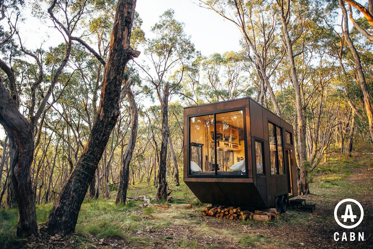 The cabin blends in with its surroundings and looks as if it belongs in the middle of nature