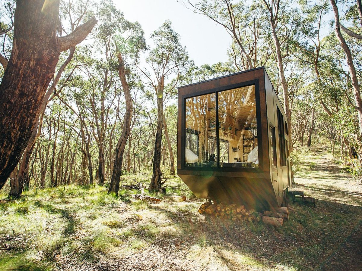 The cabin resembles a solid block with a large window on one side which brings the outdoors in