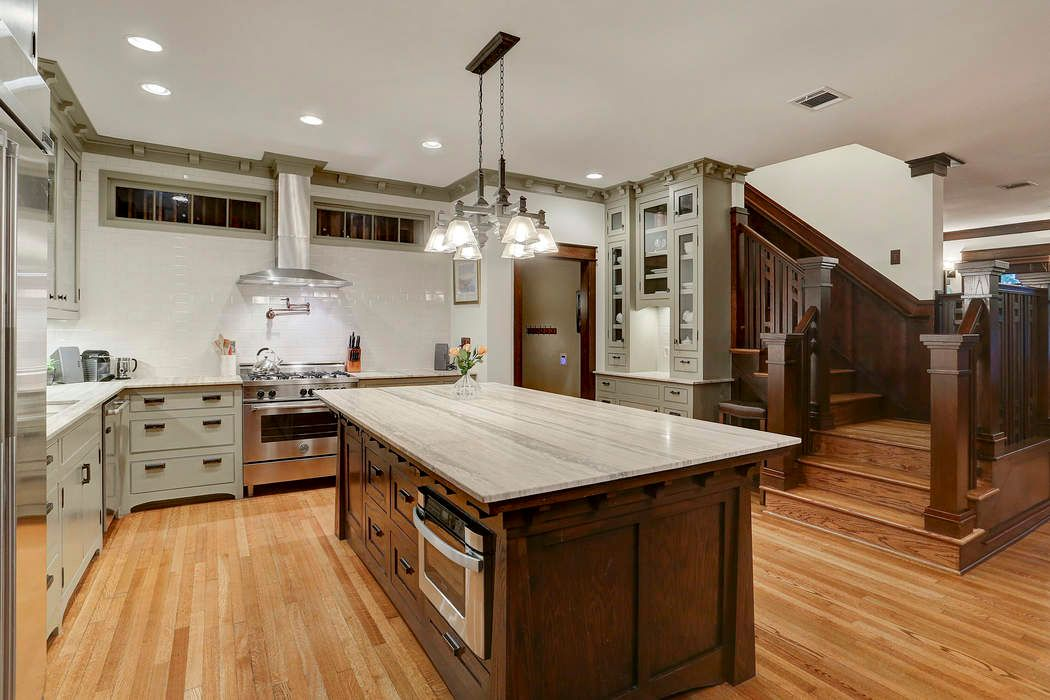 The kitchen has an L=shaped counter, off-white cabinetry and a large island with a granite countertop