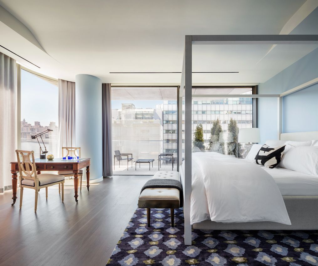The pale blue walls in this bedroom in a Zaha Hadid-designed building fit the view and setting.