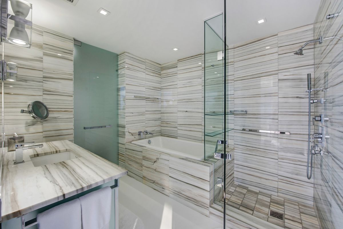 The bathrooms are lined with striated stone and feature glass shower enclosures