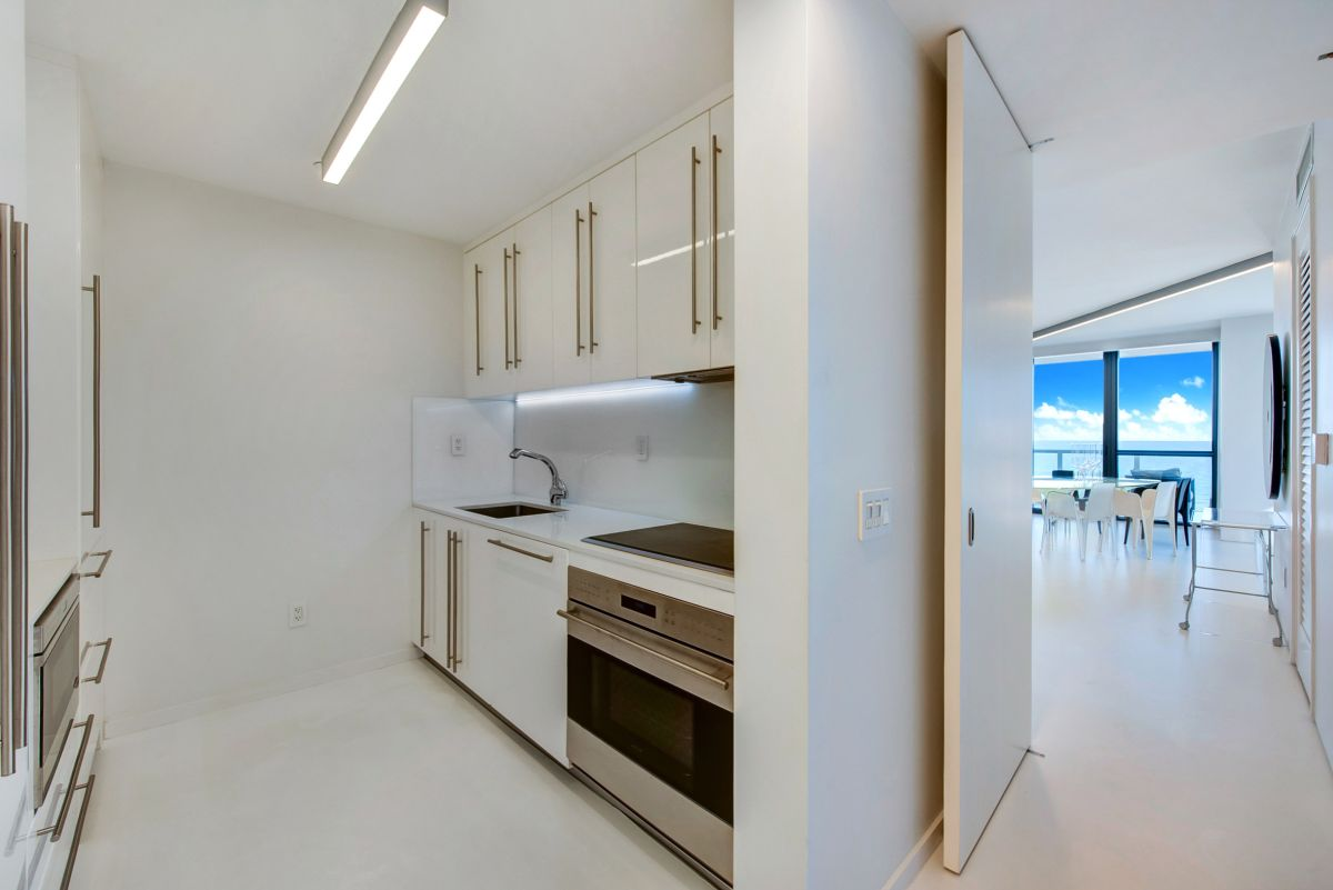The kitchen is a separate room and is an almost entirely white space