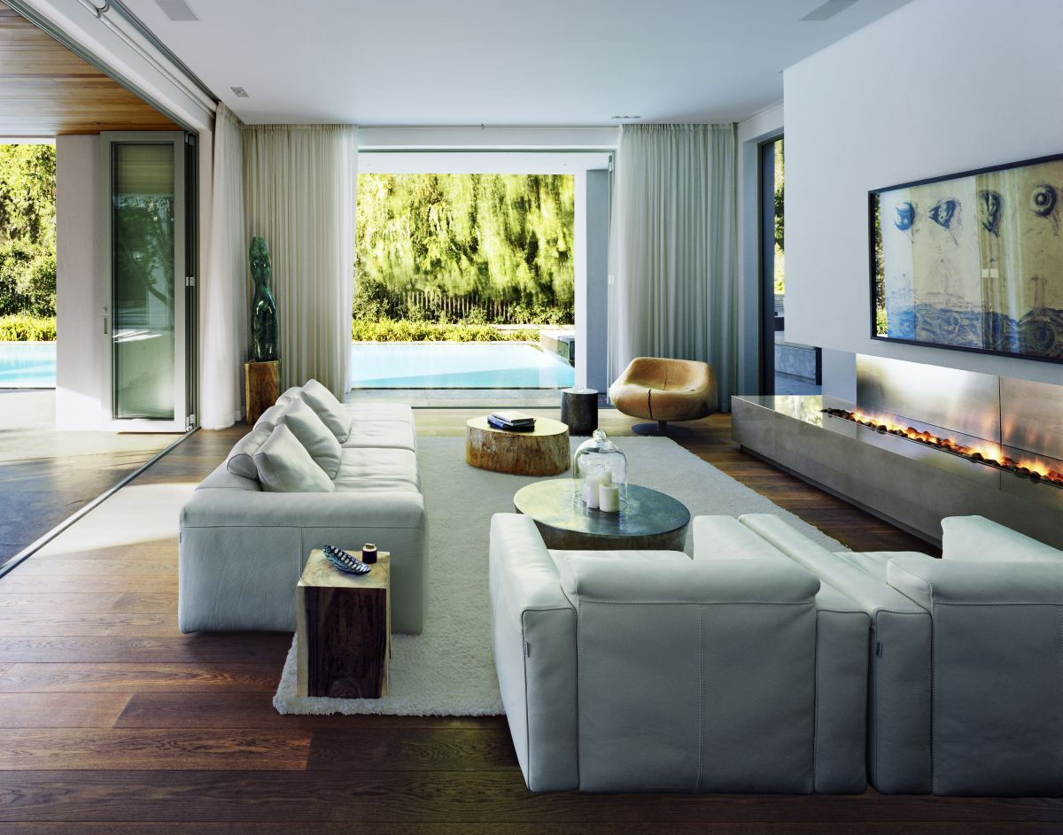 The living room has an oversized window facing the swimming pool and warm wooden floors