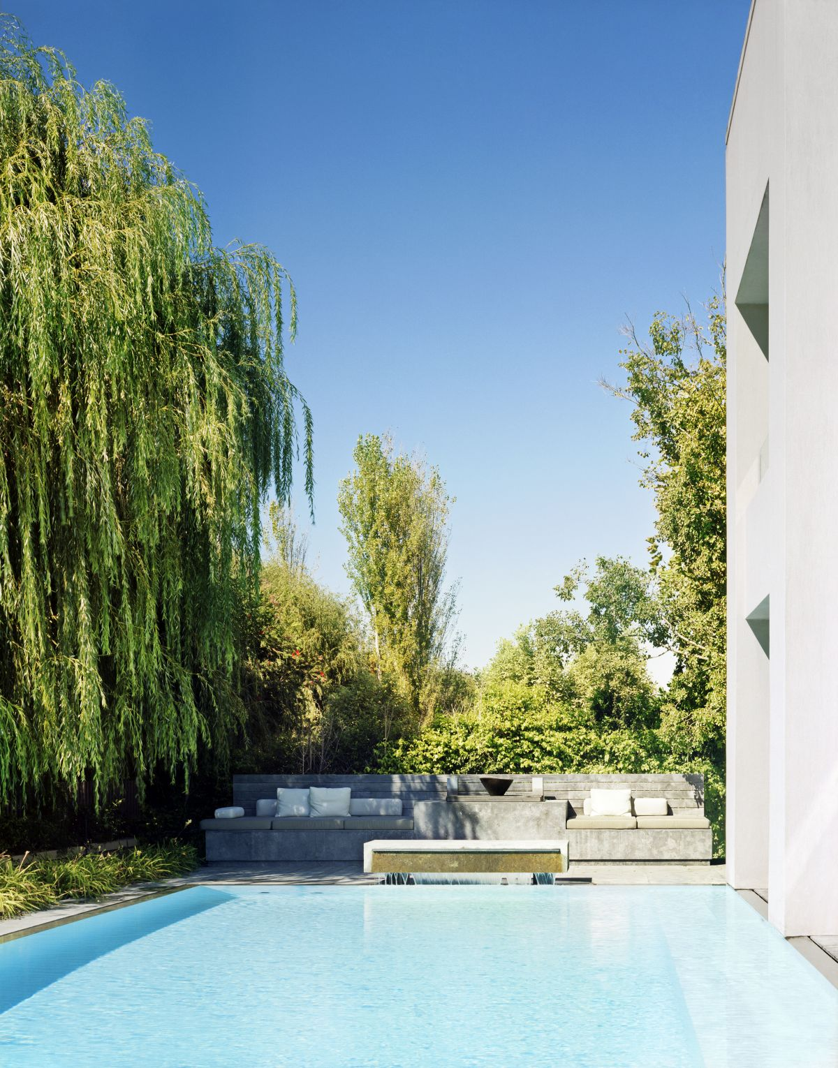 The swimming pool is exquisitely framed by trees and greenery as well as by a sculptural lounge area