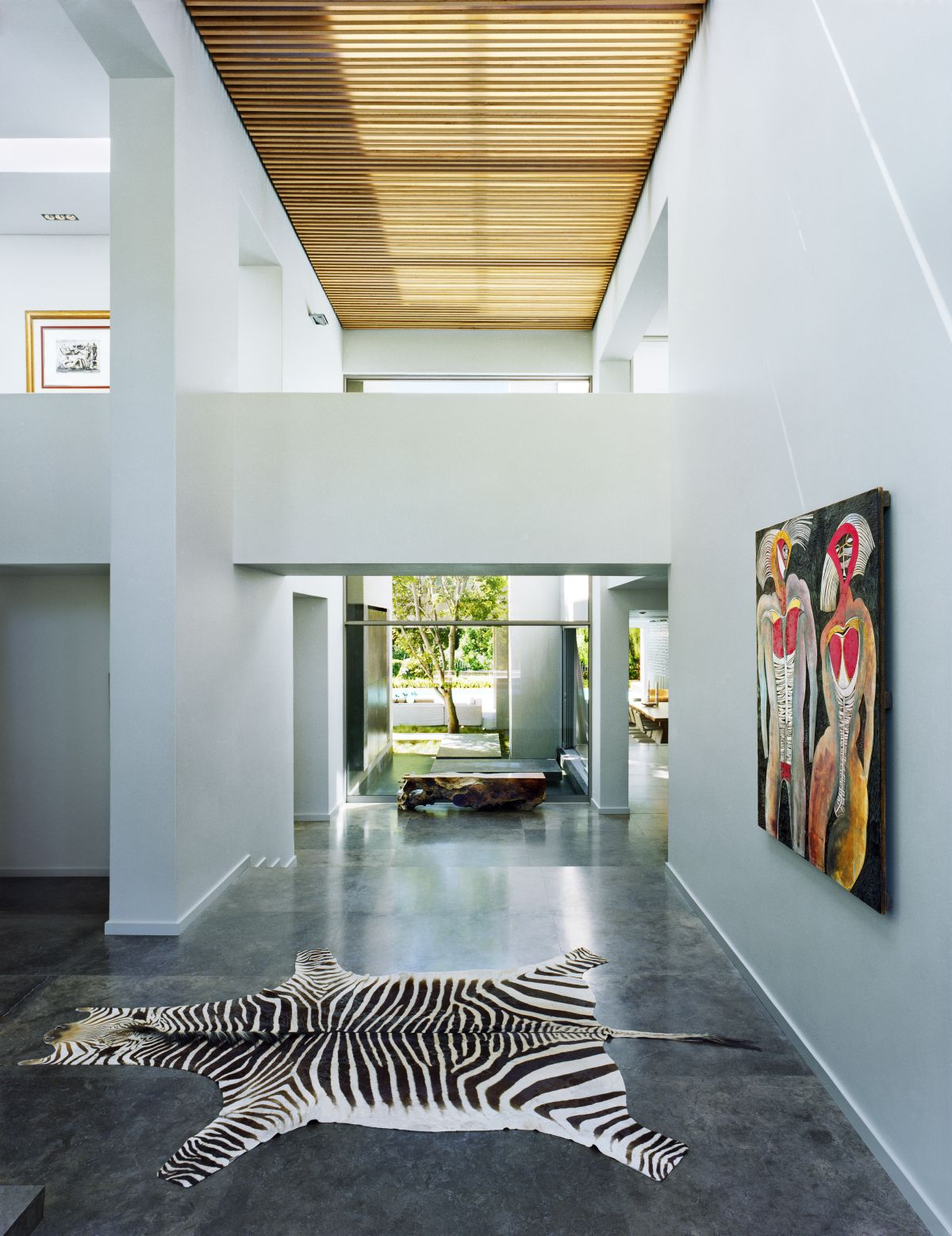 A large corridor with high ceilings is decorated with the owner's personal art pieces