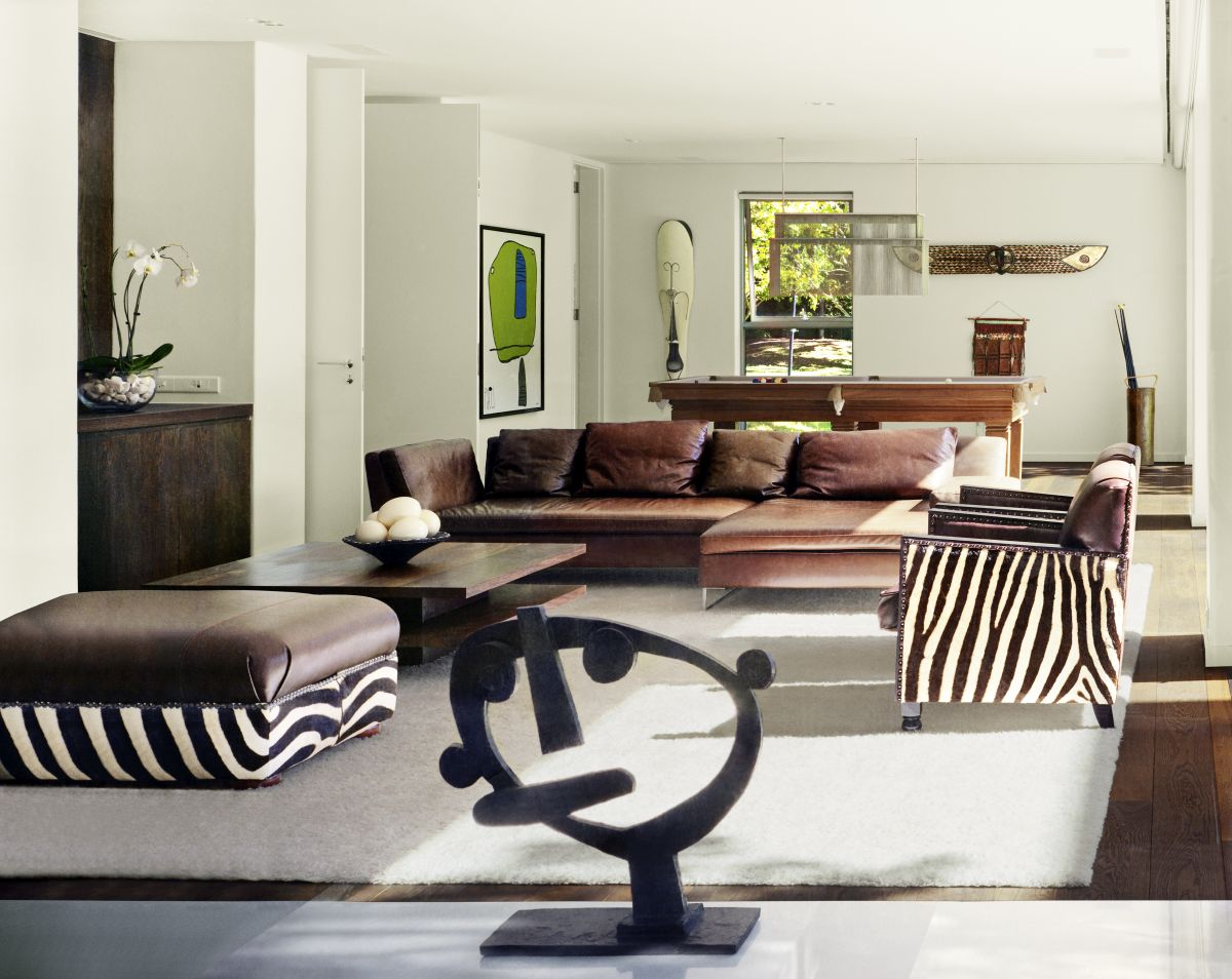 For the living room the designers chose brown leather sofas and ottomans and armchairs with zebra stripes