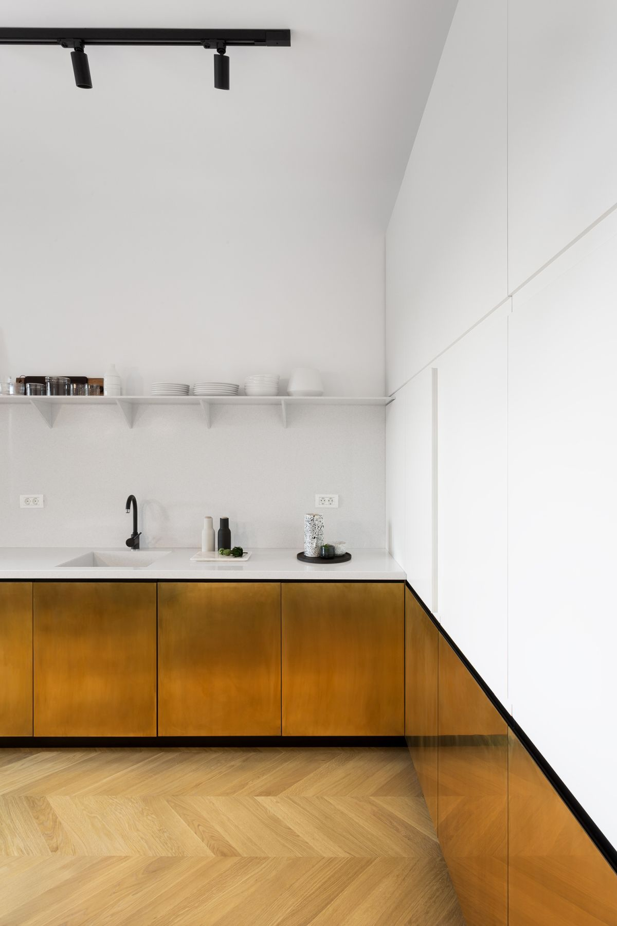 The white countertops, shelves and cabinets in the kitchen seem to disappear into the walls