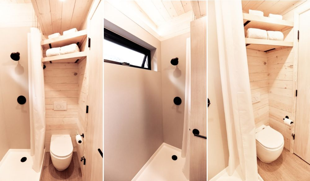 The bathroom is small but doesn't lack style. There's a modern walk-in shower with a window and towel storage above the toilet
