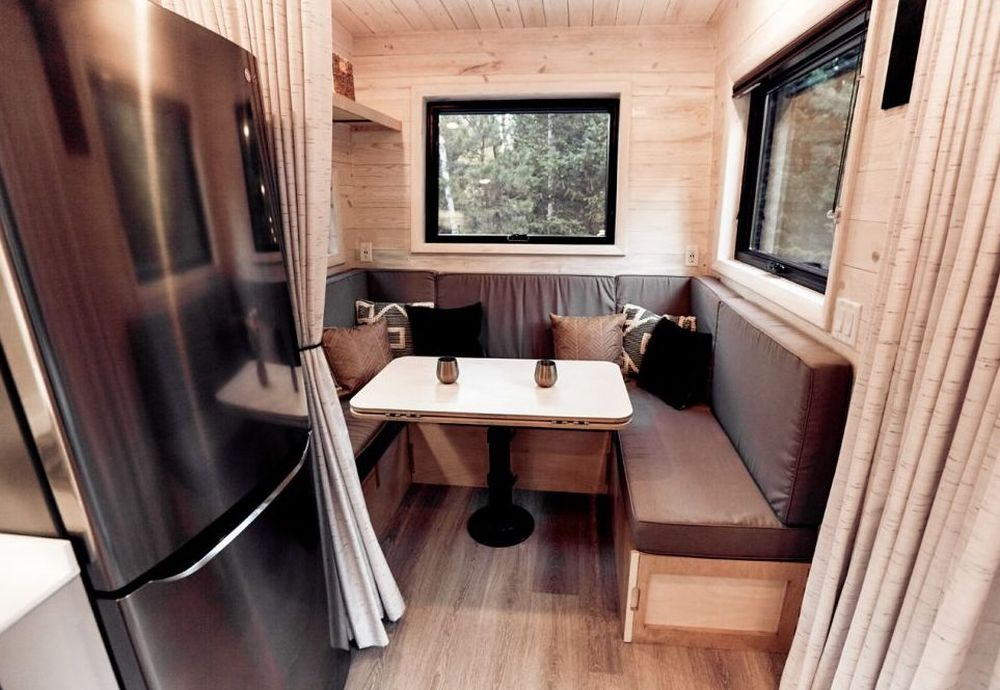 The kitchen nook has windows on two sides and a a custom built-in bench with padded seats and backrests