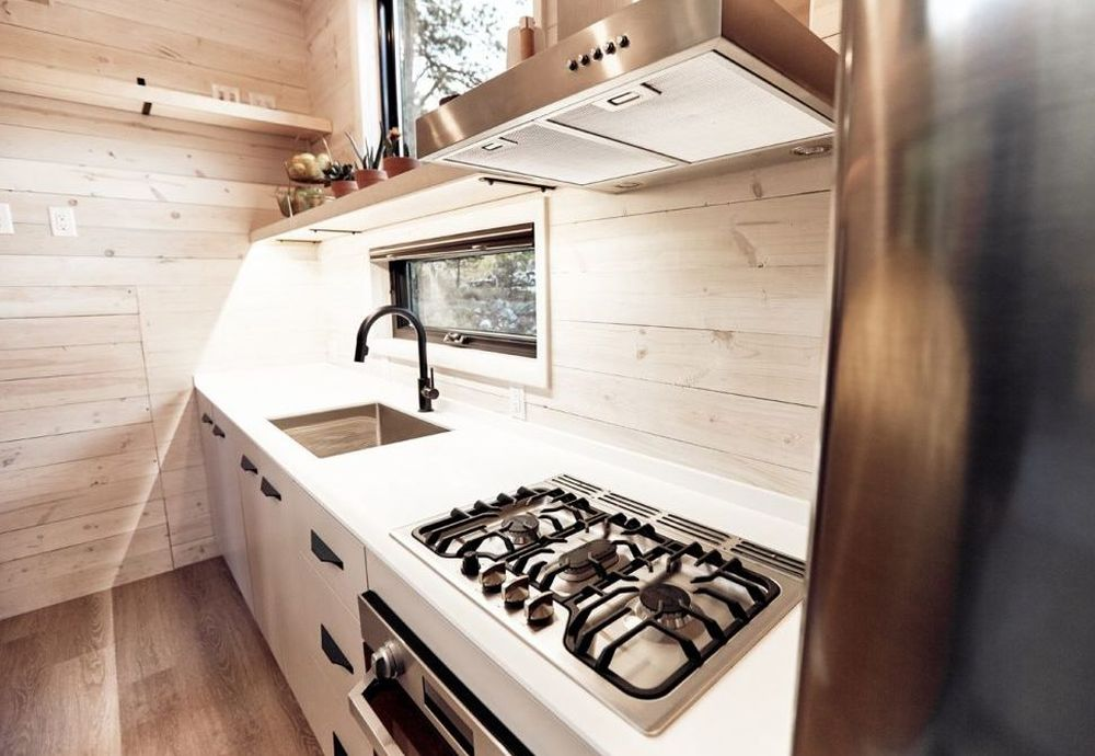 The interior is covered in whitewashed pine boards and the furniture is minimalist
