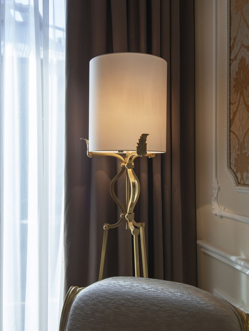 A floor lamp has an elegant brass base with leaf details.