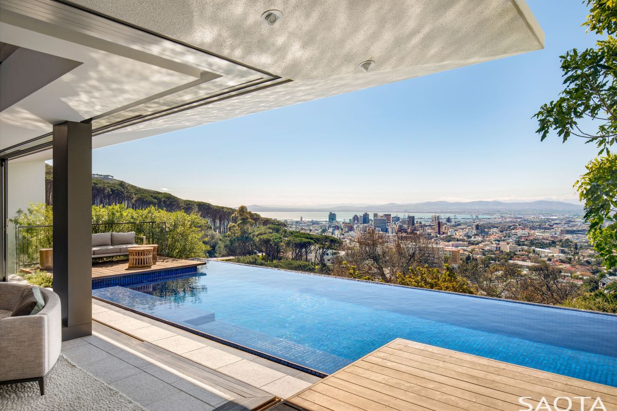 The infinity edge swimming pool stands between the living space and the city skyline