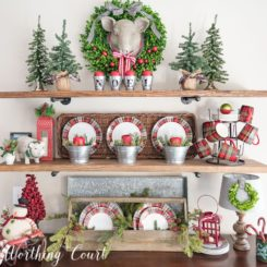 Open shelves decorated with red plates themed for Christmas