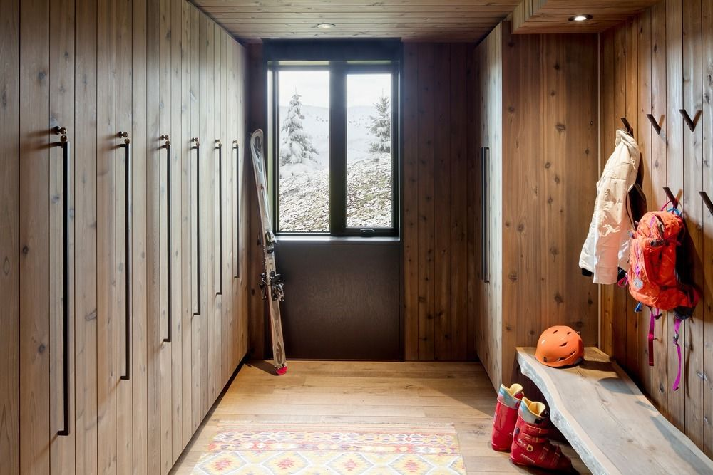 The interior is welcoming and cozy right from the entryway, featuring wood-paneled walls and a live-edge bench