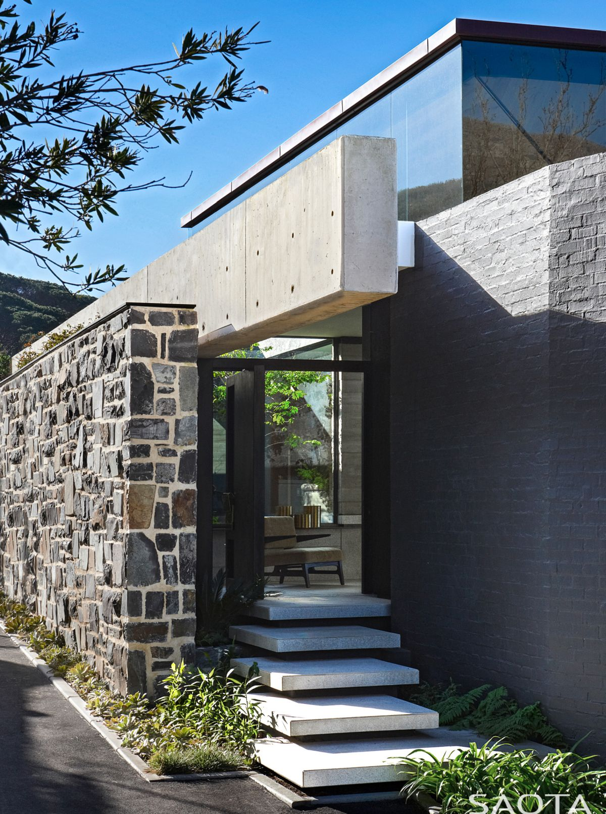 A stone wall conceals most of the house on the street side, offering privacy for the bottom floors