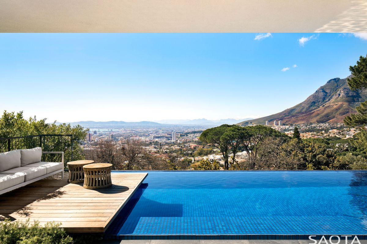 The house also featuring this amazing infinity edge pool and a small wooden deck
