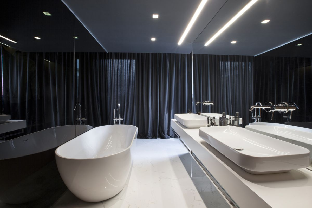 Long curtains and large mirrors make this bathroom appear large and very comfortable-looking