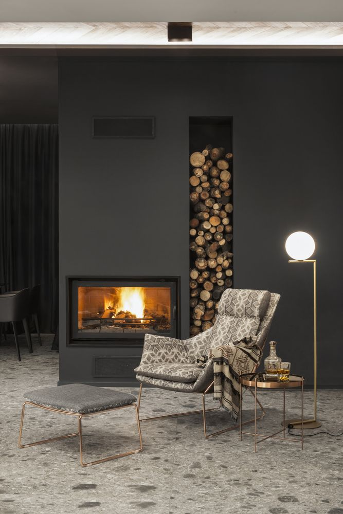 A fireplace creates a very warm and welcoming ambiance and a built-in wall niche offers storage for the firewood