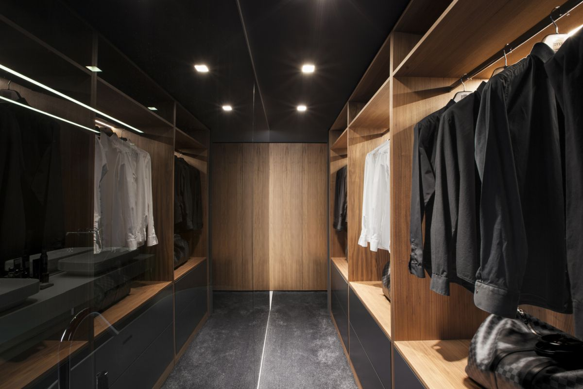 A large walk-in closet features an entire wall of mirrors and this makes it seem larger than it actually is