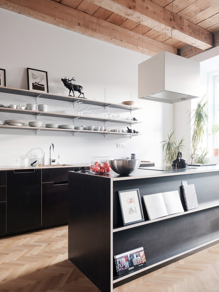 The light wood surfaces are complemented by white walls and black furniture