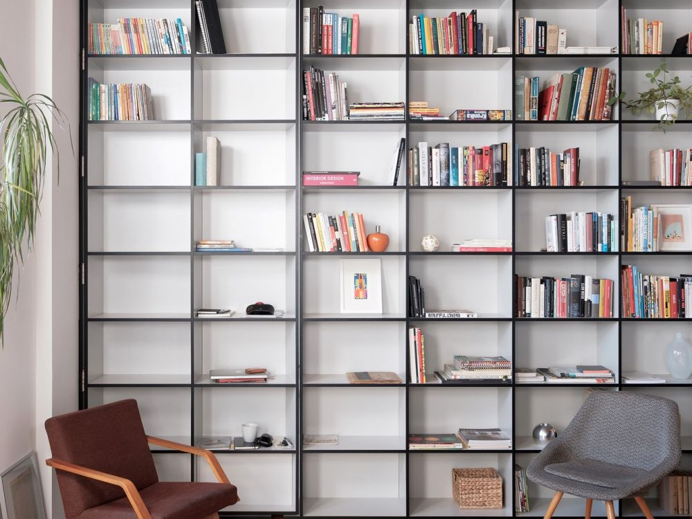 The full-height bookcase is seamlessly built into the wall and the Murphy door adds mystery to its design