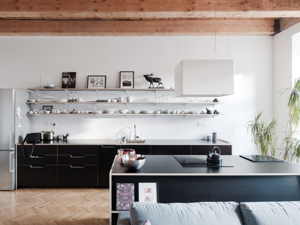 The kitchen has sleek wall-mounted shelves which add storage while maintaining an open look