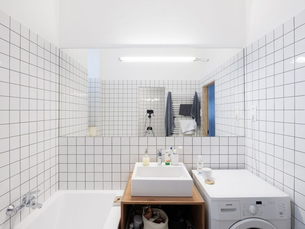 The bathroom is small but has an airy and open look thanks to the white tiles and large mirror