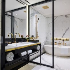Bathroom with marble walls and gold fixtures