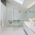 White bathroom with glass shower doors and sky lighting