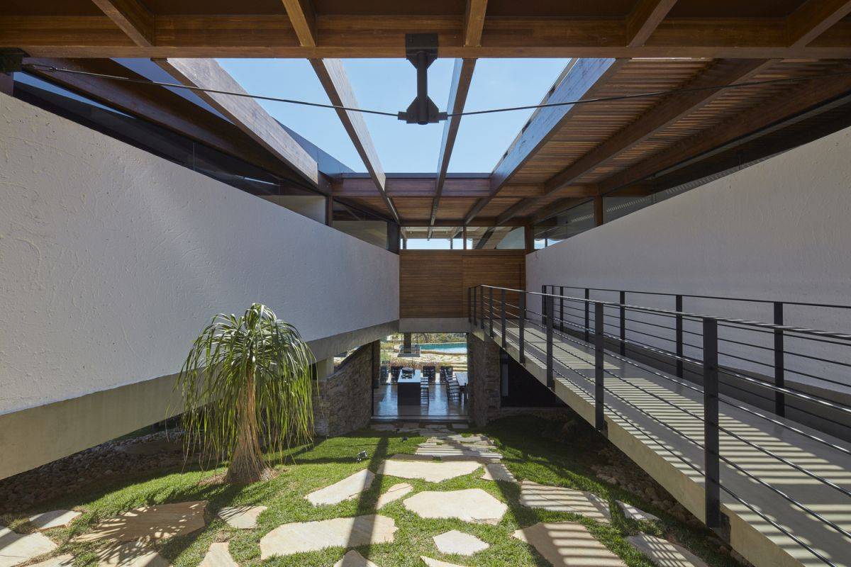 The house embraces the sloping ground and has this large void which leads to the entryway