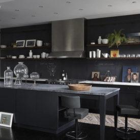 Black kitchen with chalkboard backsplash and open shelves from wood