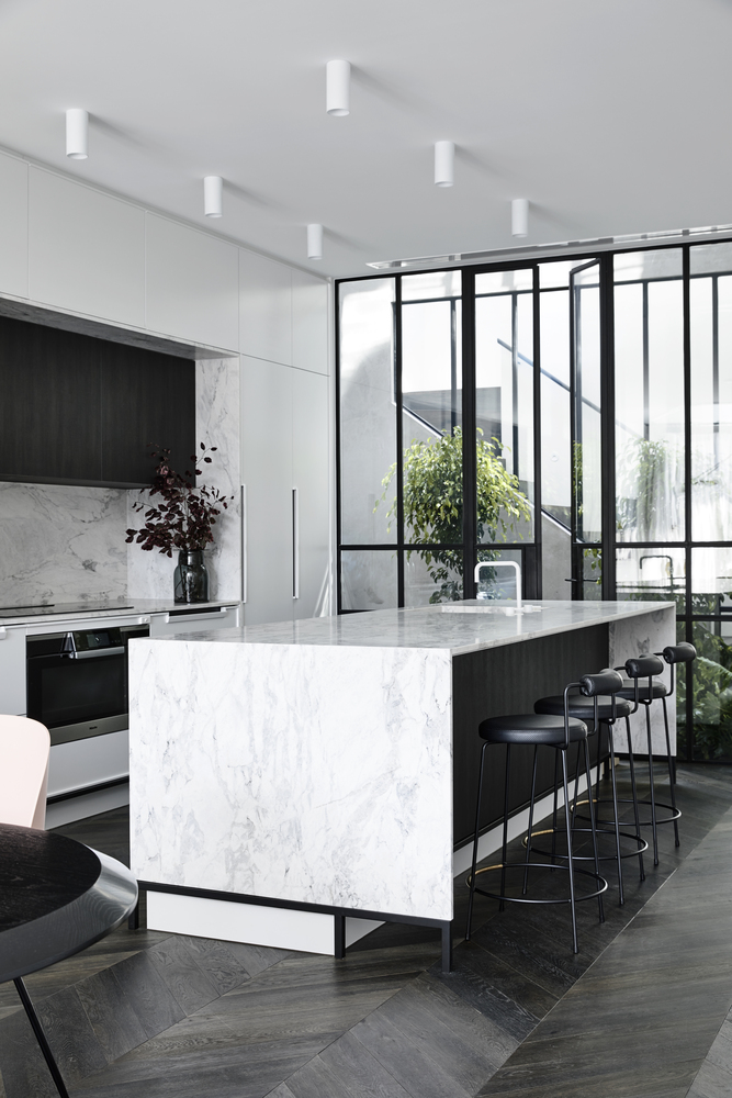 The kitchen has an open design and an elegant island with a waterfall-style marble countertop