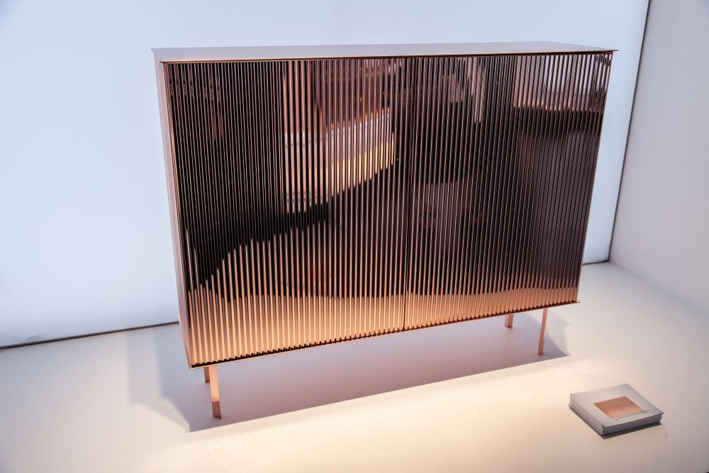 A small chest of drawers with a polished copper finish