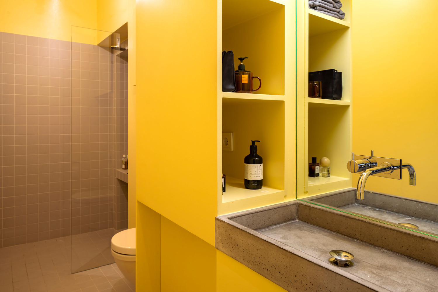 The bathroom has a built-in storage wall which gives the room a wholesome and organized look