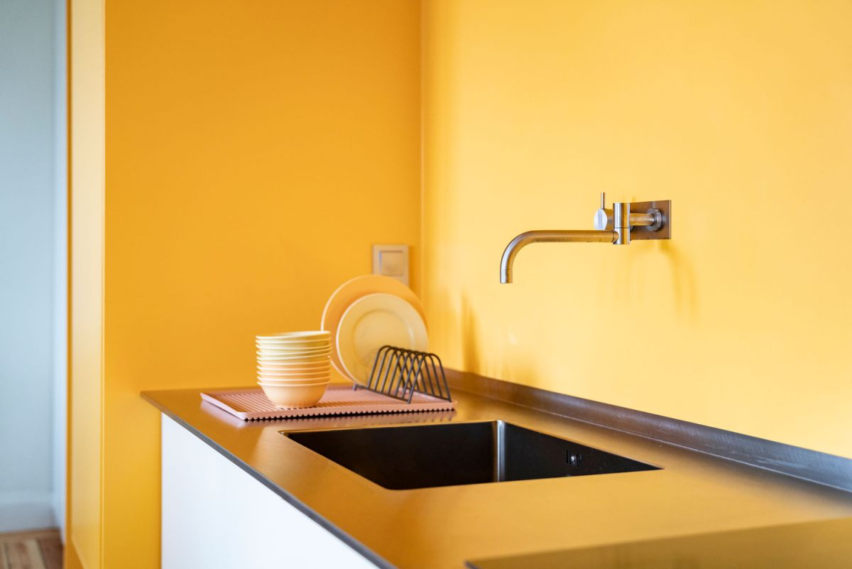 The warm yellow tone of the walls is reflected into the kitchen counter adding a