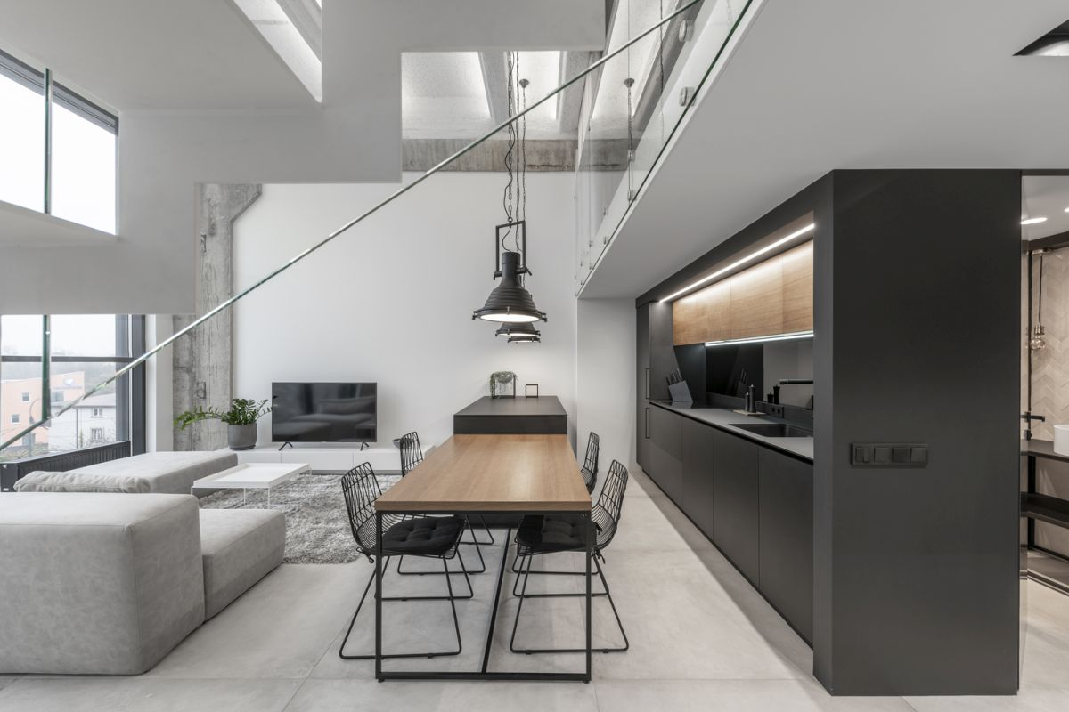 The living area is a double-height space with large windows and light-colored surfaces
